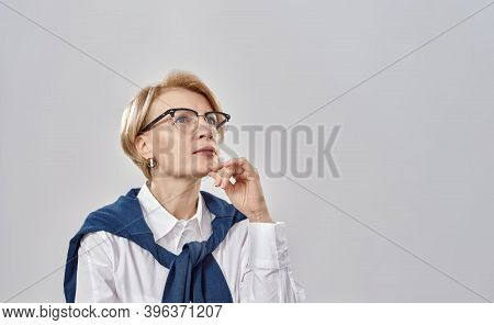 Portrait Of Elegant Middle Aged Caucasian Woman Wearing Business Attire And Glasses Having A Serious