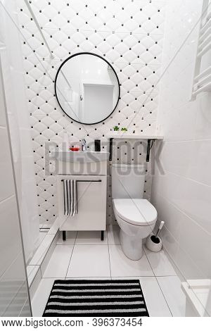 Part Of A Small New Modern Bathroom. The Main Colors - White And Black. Tiled Walls And Floors. Cabi