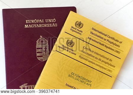 Bogota, Colombia - Circa 2019: Showing passport and vaccination certificate booklet issued by WHO listing vaccines given for traveling around the world, showing documents at immigration control