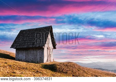 Picturesque autumn meadow with old wooden house and clear sky in the Carpathian mountains, Ukraine. Landscape photography