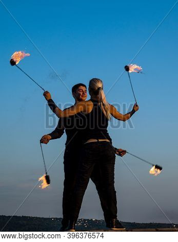 Sensual Couple Of Fire Performers Perform Dance With Flaming Poi On Blue Sky Outdoors, Desire