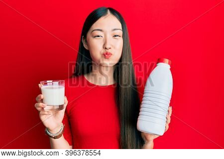 Young chinese woman drinking a glass of fresh milk puffing cheeks with funny face. mouth inflated with air, catching air.