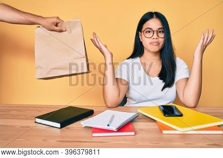 Young beautiful asian girl sitting on the table stuying getting take away food clueless and confused with open arms, no idea and doubtful face.
