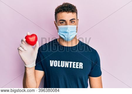 Handsome young volunteer man wearing volunteer t shirt puffing cheeks with funny face. mouth inflated with air, catching air.