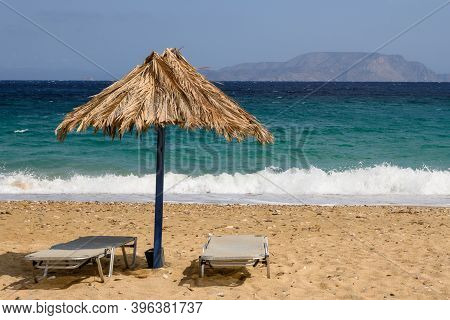 Sun Beds And Umbrella At Agia Theodoti Beach On Ios Island. A Wonderful Beach With The Golden Sand A