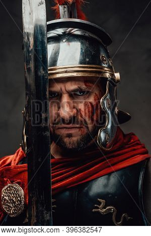 Serious And Angry Roman Soldier Dressed In Dark Armour With Helmet And Red Mantle Posing Looking At