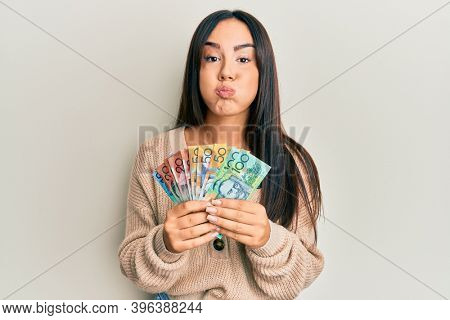 Young beautiful hispanic girl holding australian dollars puffing cheeks with funny face. mouth inflated with air, catching air.