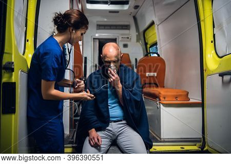 A Young Female Paramedic On Duty, Taking Care Of An Injured Man.