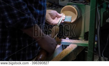 Professional Man Carpenter Hands Using Skew Chisel For Shaping Piece Of Wood On Wood Turning Lathe A