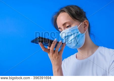 Woman In Medical Face Mask Holding Smartphone Device, Using Voice Recognition Function, Recording Au