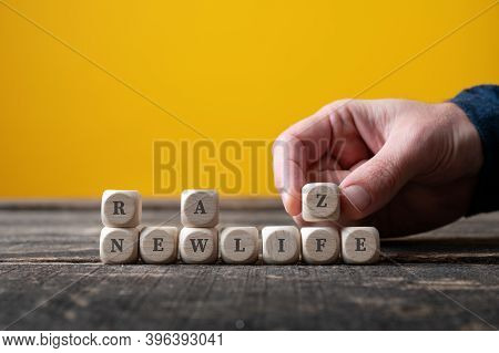 Male Hand Assembling Wooden Cubes To Spell New Life Changing Into The Word Realize.