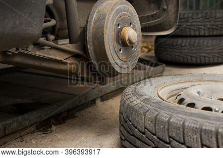 Car On Tire Mounting With Removed Wheel. Wheel Hub Closeup. Seasonal Tire Change. Empty Rusty Hub Wi
