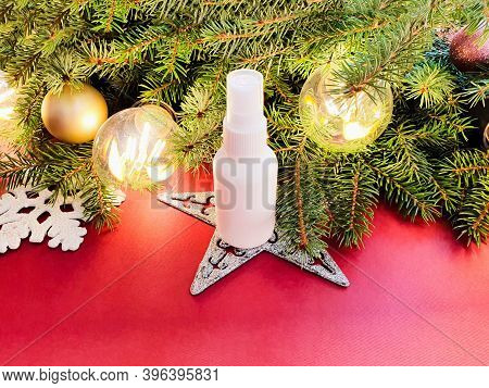 Mockup Of White Plastic Spray Bottle, Christmas Fir Tree And Christmas Decorations On A Red Backgrou