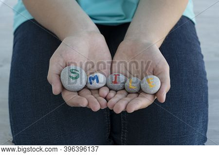 Close Up Image Of Young Female Hands Hold Gray Round Stones With Letters On Them And Inscription Smi
