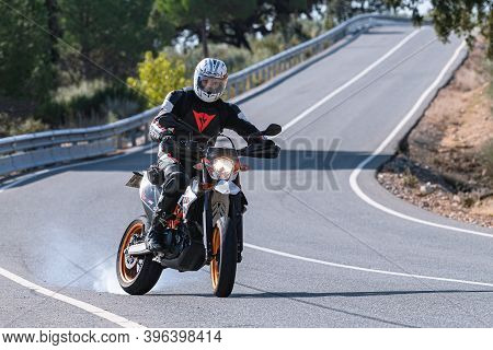 Motorcycle In The Foreground With Biker Competing On Open Road..