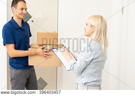 Woman Receiving Boxes From Postman At The Door In Home Delivery Concept. Woman Received The Parcel F