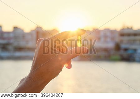 Yellow Gel Capsule Vitamin D Omega-3 In Womans Hand, Sun Sea Background.