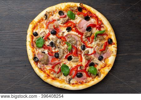 Italian Pizza With Melted Mozzarella Cheese, Green Olives And Tomatoes, Garnished With Fresh Vegetab
