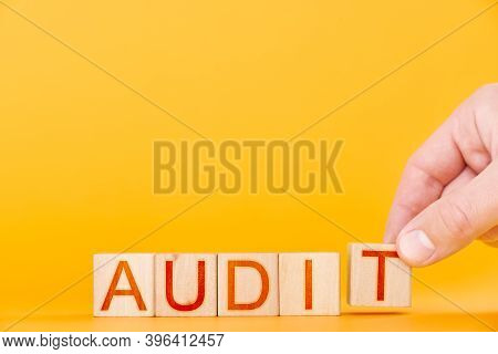 Audit. Man Puts Wooden Cubes Into The Word Audit On Orange Background