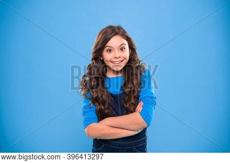 Kid Girl Long Hair Posing Confidently. Girl Curly Hairstyle Feels Confident. Child Hold Hands Confid