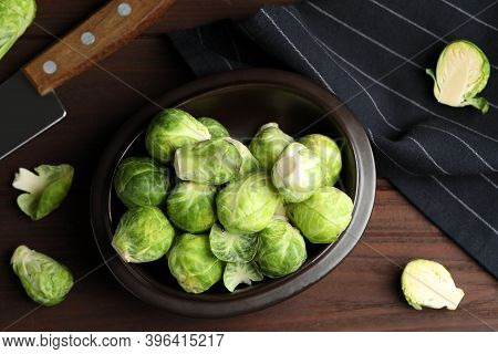 Fresh Brussels Sprouts On Brown Wooden Table, Flat Lay