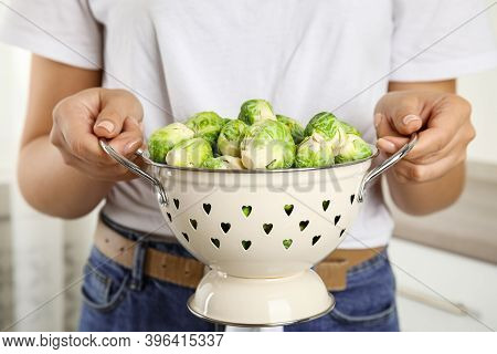 Woman Holding Colander With Brussels Sprouts On Blurred Background, Closeup