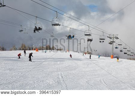 LA PLAGNE, FRANCE - CIRCA 2016: Ski lifts and skiers in the bright sunlight on a slope with good view over the mountains. Part of Paradiski ski resort, one of the biggest in Europe