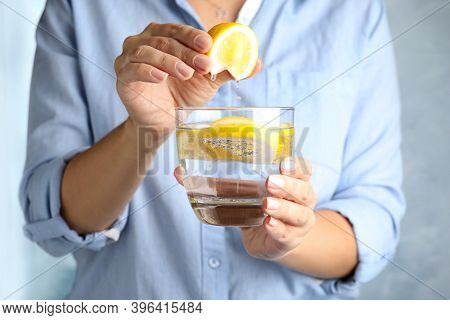 Woman Squeezing Lemon Juice Into Glass Of Soda Water, Closeup
