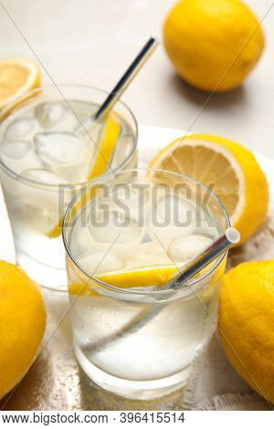 Soda Water With Lemon Slices And Ice Cubes On Table