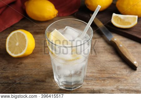 Soda Water With Lemon Slices And Ice Cubes On Wooden Table