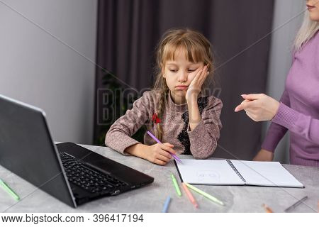 A Mother Consoles Her Young Daughter When She Gets Discouraged Trying To Do Her Homework.