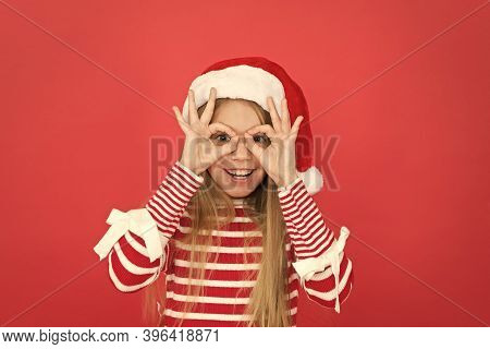 Party Fun. Happy Kid Make Glasses Gesture Red Background. Little Girl Enjoy Santa Claus Party. New Y