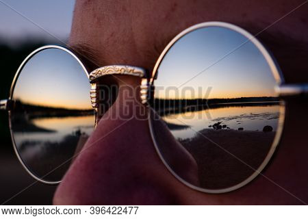 A Man With Glasses, Glasses Close-up. Reflection In The Glasses Of The Coast And A Beautiful Sunset.