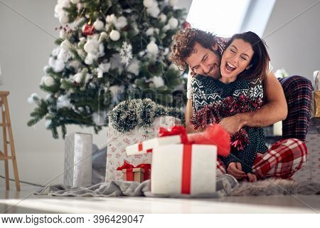 A young couple in love enjoying Christmas morning at home in a cheerful atmosphere. Christmas, relationship, love, together