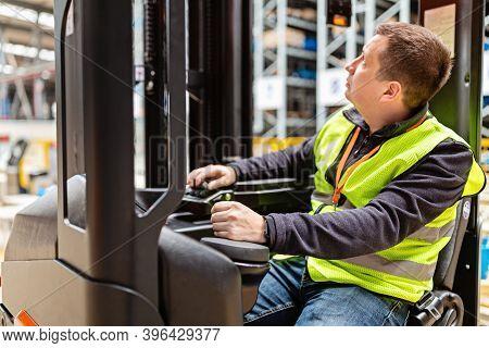 Storehouse Employee In Uniform Working On Reachtruck In Modern Automatic Warehouse. Warehousing, Mac