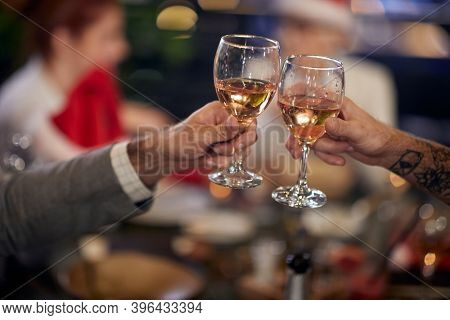 A group of colleagues drinking and eating  at New Year's company dinner in a holiday atmosphere at a restaurant. Together, New Year, celebration