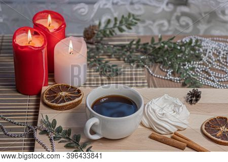 Christmas Candles, A Mug Of Coffee On A Wooden Table, Airy Meringue, Dried Orange Slice, Cinnamon An