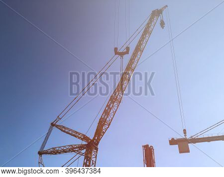 Tower Cranes And Blue Sky With Sun Flare. Lifting Machinery At Construction Site