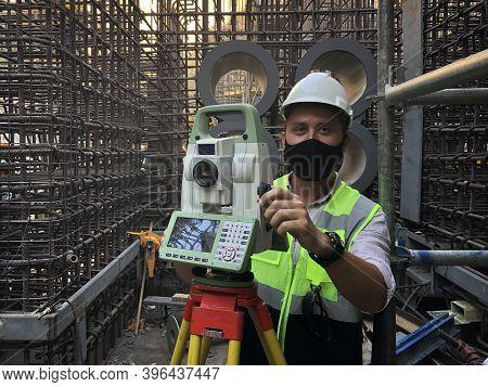 Land Surveyor Dressed In Hardhat, Mask And Protective Vest Works On Total Station