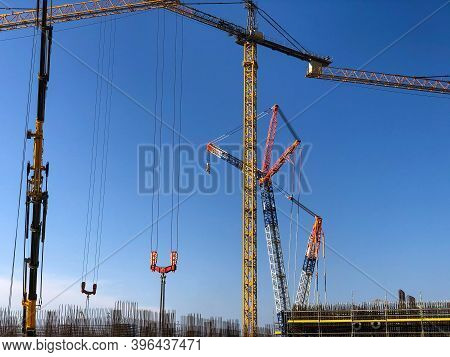 Lots Of Tower Cranes Against Blue Sky. Lifting Machinery At Construction Site