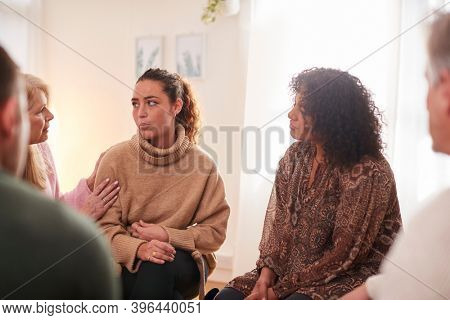 Group Consoling Woman Speaking At Support Group Meeting For Mental Health Or Dependency Issues