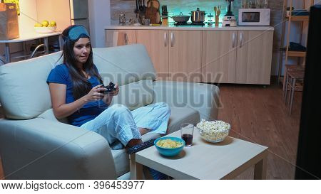 Woman Sitting On Sofa Playing Video Game Late At Night Wering Eye Mask On Forehead. Excited Determin