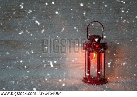 Christmas Lantern And Falling Snow On Wooden Wall With Copy Space. Red Lantern And Snowflakes On Vin