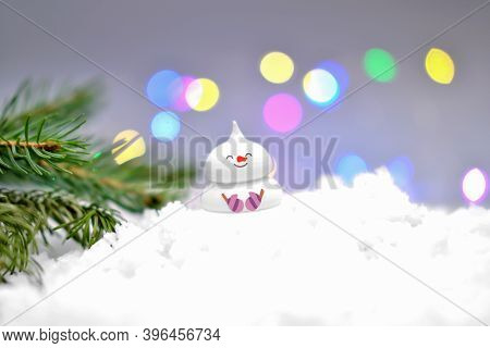 Cute Edible Snowman On The Snow And Christmas Tree Branch. Bokeh Lights. Holiday Selebration And Mer
