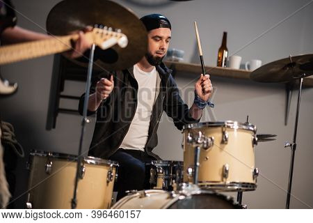 A Boysband Of Guitarist, Bassist, And Drummer Rehearse In Their Garage