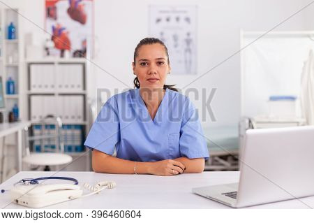 Portrait Of Pretty Medical Nurse Smiling At Camera In Hospital Office Wearing Blue Uniform. Healthca