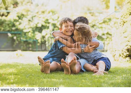 Three Little Kids Are Hugging Together Outdoors