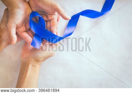 Hands Holding Deep Blue Ribbon On White Fabric With Copy Space. Colorectal Cancer Awareness, Colon C