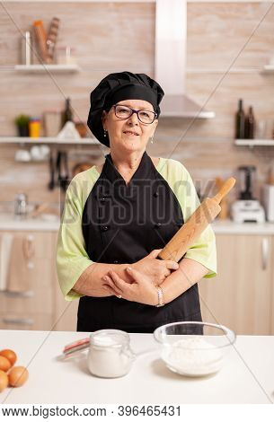 Professional Baker Smiling At Camera In Home Kitchen Wearing Apron And Bonete. Retired Elderly Baker