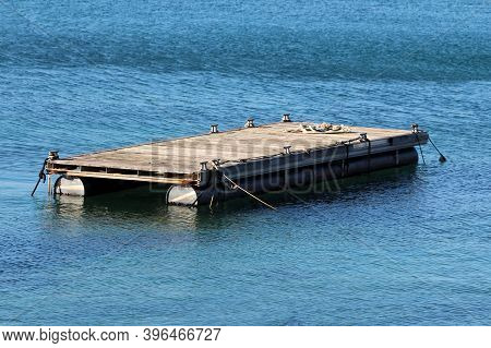Elongated Homemade Makeshift Old Floating Pier Made From Empty Metal Barrels And Dilapidated Narrow